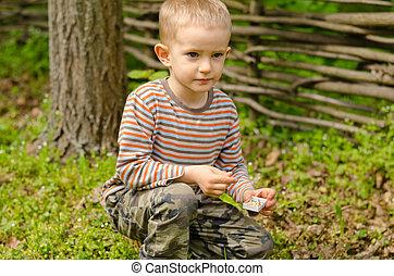 Little boy starting a campfire