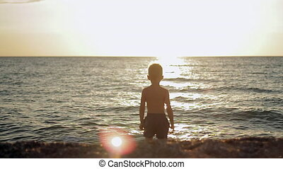 Little boy stay in calm sea at sunset.