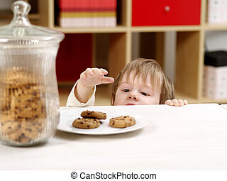 Photo of a nineteen-month-old stealing cookies from a plate on a table with a full cookie jar beside.