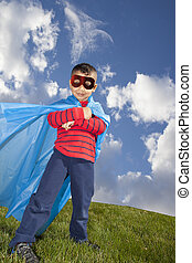 little boy superhero against blue sky