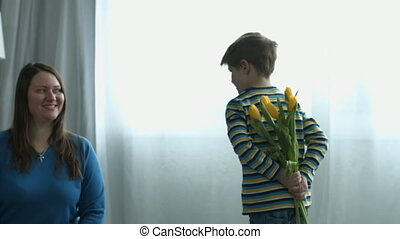 Little boy surprises mother with flowers at home