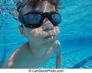 Little boy swims underwater in the pool