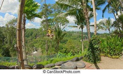 Little boy swing on big swings in a tropical surrounding