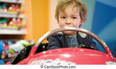 Little boy swinging in a toy car in the shop
