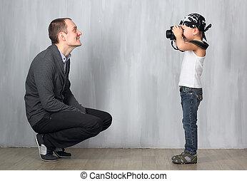 Little boy takes a photo of a man