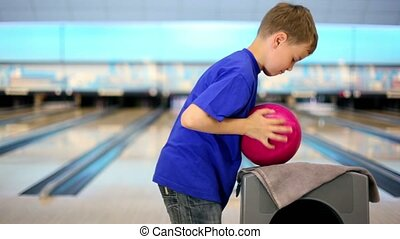 boy takes ball and throws it to beat skittles on bowling...