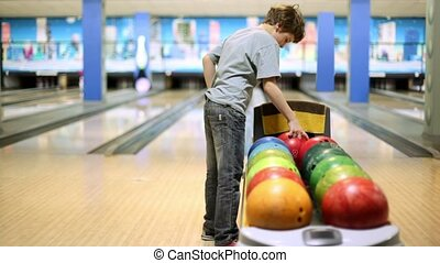 Little boy takes bowling ball and throws it to beat skittles