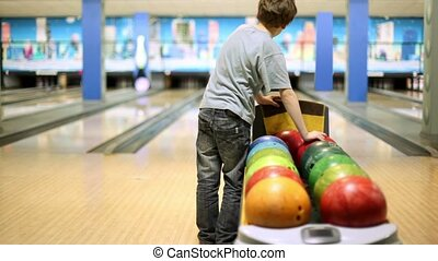 Little boy takes one of bowling balls and throws it to beat tenpins