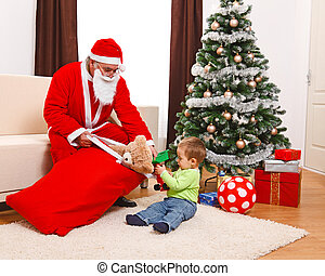 Little boy taking out toys from Santa's bag