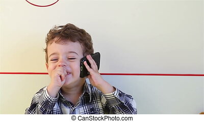 Little boy talking on smartphone - Laughing little boy...