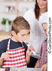 Little boy tasting the baking