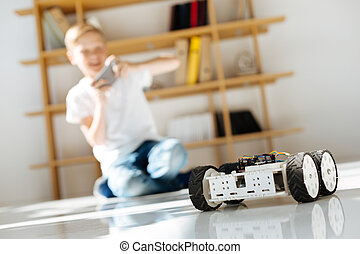 Little boy testing his robotic vehicle toy