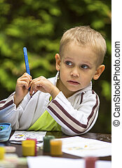 Little boy thinking with a pencil