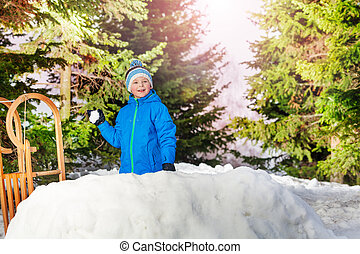 Little boy throw snowball hiding behind snow wall - Happy...