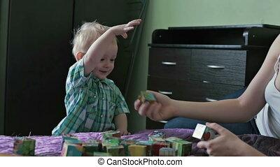 Little boy throw toy cubes