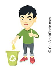 Little boy throwing banana peel in recycling bin.