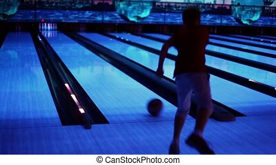 Little boy throws bowling ball and jumps after last skittle...