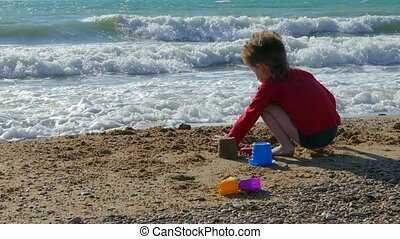 Little boy throws sand on the beach