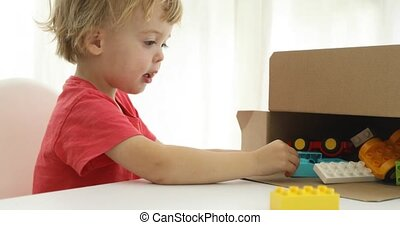 Little boy tidying up his toys in a box - Little boy tidying...