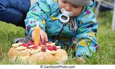 Little boy tries to take cake on his first birthday in the park in slowmotion. 1920x1080
