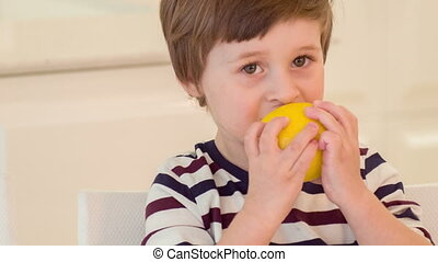 Little boy trying to bite lemon - This is funny. Little boy...