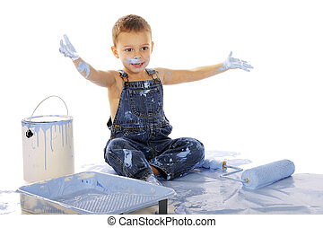 An adorable preschooler sitting among wall-painting supplies. He's happil clapping his paint-soaked hands. Isolated on whitel.