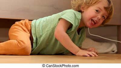 Little boy under the bed - Little boy crawls out from under...
