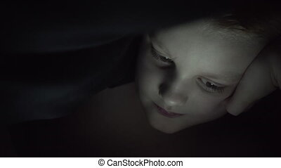 Little Boy Under The Covers At Night With A Digital Tablet Playing Game