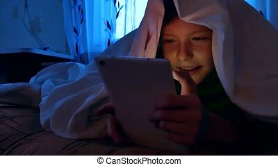 little boy under the covers at night with a digital tablet...