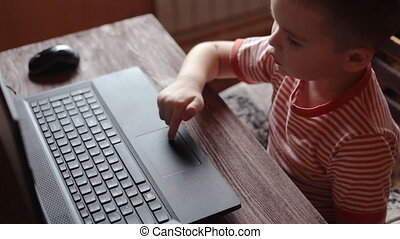 Little boy uses a laptop at home