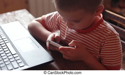 Little boy uses smartphone at home