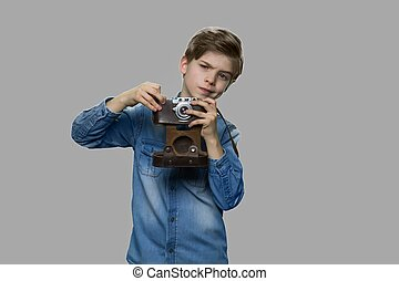 Little boy using film camera on gray background.