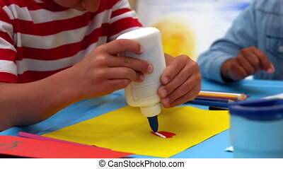 Little boy using glue in classroom