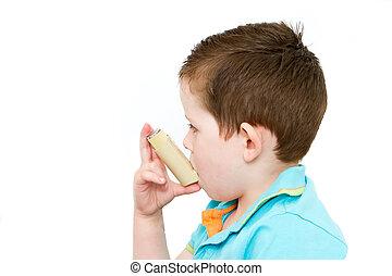 little boy using his asthma pump