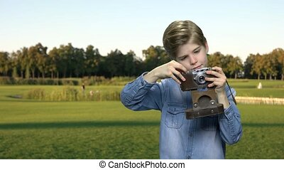 Little boy using photo camera outdoors.