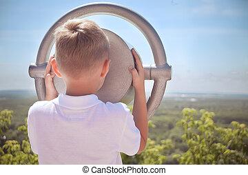 little boy using seaside tourist viewer operated binoculars outside