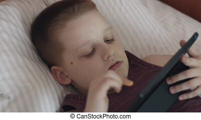 Little Boy Using Tablet Computer Lying In Bed