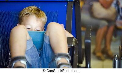 Little boy using touchpad in waiting room - Little boy in...