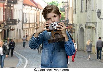 Little boy using vintage camera outdoor.