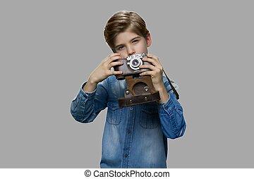 Little boy using vintage camera.