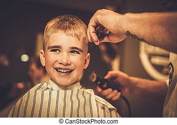 Little boy visiting hairstylist in barber shop