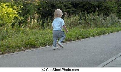 Little boy walking along the road in the park