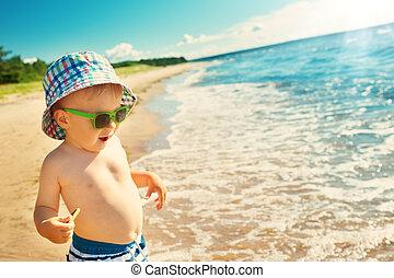 little boy walking at the beach in summer hat