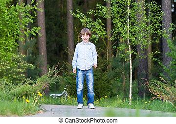 Little boy walking in a beautiful forest