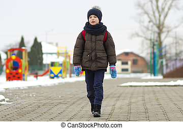 Little boy walking in the park. Child going for a walk after school with a school bag in winter. Children activity outdoors in fresh air. Healthy way of life concept.