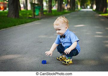 little boy walking in the park in summer