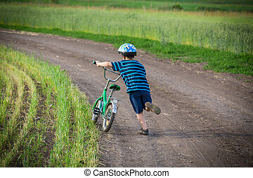 Little boy walking uphill with his bike on rural landscape