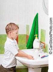 little boy washes in a bathroom