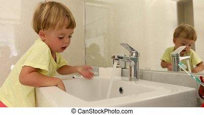 Little boy washing his hands in bathroom