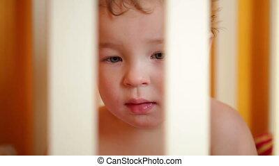 Little boy watching a film in the playpen.